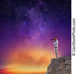 fotógrafo, tomar una foto, en, un, cielo de la noche, lleno, de, estrellas