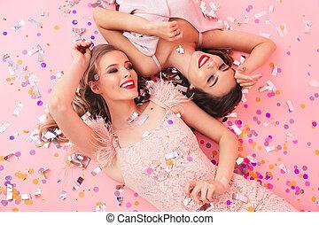 foto, de, dos, mujeres jóvenes, en, vestidos, sonriente, y, mentira en el piso, debajo, caer, colorido, confeti, o, lentejuelas, aislado, encima, fondo rosa
