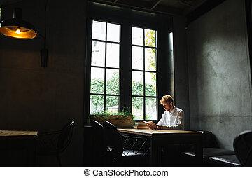 foto, de, jovem, readhead, homem enfrentado, em, camisa branca, lendo um livro, em, cafeteria