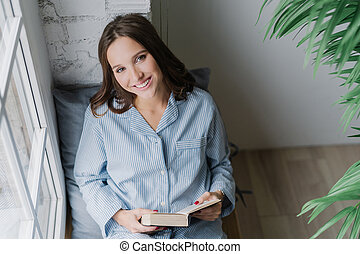 foto, di, allegro, donna, leggere, romantico, storia, prese, libro, porta, vestiti casuali, pose, su, davanzale finestra, in, confortevole, room., vista, da, above., soddisfatto, femmina, modello, essendo, in, buon umore, leggere, textbook.