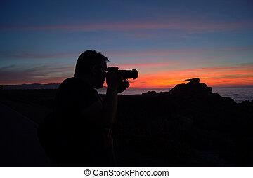 fotografo a contraluz con puesta de sol de fondo
