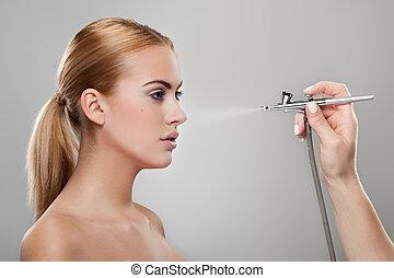 Foundation spray - Make-up artist spraying foundation on a...
