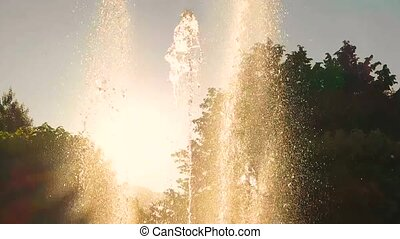 Fountain and sunlight. Water splashes in slow motion....