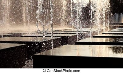Fountain backlit. Falling water sunlit by sunset