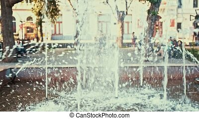 Fountain in city park with unrecognizable young girl walking...