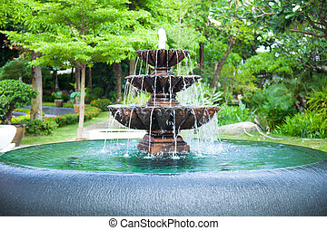 fountain in the garden. Trees of various sizes and types....