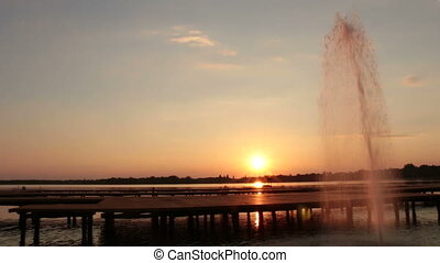 Fountain in the lake at sunset