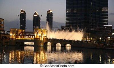 fountain near Burj Dubai with illumination of the city in Dubai, UAE