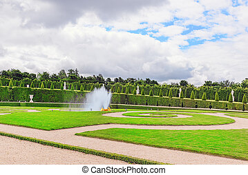 Fountain near the flower bed in a Famous Gardens of Versailles (Chateau de Versailles).