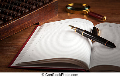 fountain pen and diary on a table with an abacus and loupe