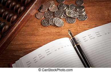 fountain pen and diary on a table with an abacus and ruble coins