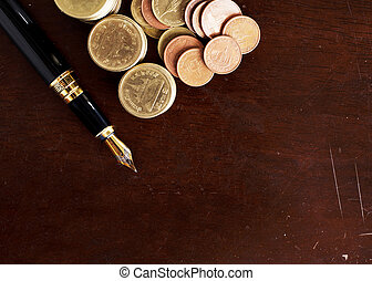 Fountain pen and Money coins stack on wooden table for finance concept background bove