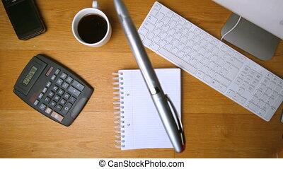 Fountain pen falling onto notepad on office desk beside...