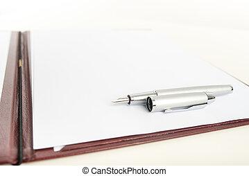 Fountain pen lying on blank paper