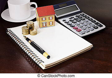 Fountain pen with coins stack and paper house and calculator and coffee cup on wooden desk table