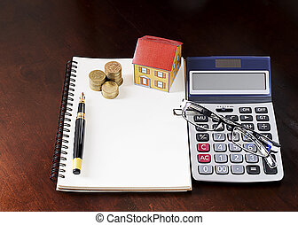 Fountain pen with coins stack and paper house and calculator and glasses on wooden desk table
