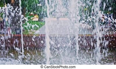 Fountain slow-motion wih blurred park on background -...