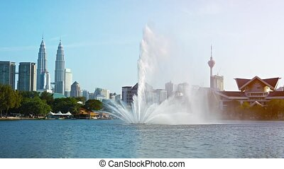 UltraHD video - Beautiful fountain, spraying jets of water towards the sky from the middle of a pond in a downtown, city park.