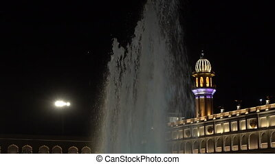 Fountain sprays water in courtyard. - Tower and fountain in...
