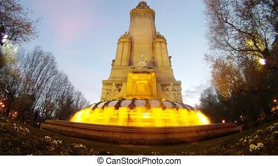 Fountain stands against blue sky at sunset, time lapse
