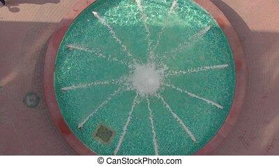 Fountain water aerial closeup drone bird eye top view landing down rotation camera movement