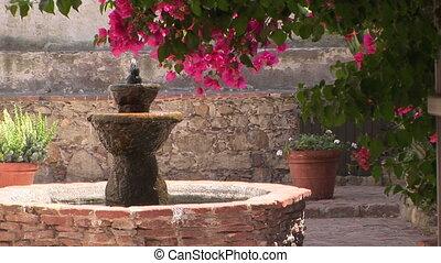 Water fountain in a brick courtyard in San Juan Capistrano