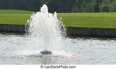 Fountain water splashing on lake surface
