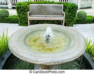 Fountain with wooden bench in garden