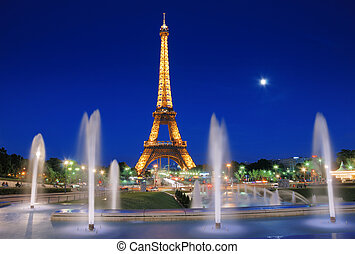 The Eiffel Tower and fountains de Varsovie seen at evening in Paris, France. The fountain was built in front of the Chaillot Palace for the Universal Exposition of 1937. It consists of a series of terraced basins with twenty water canons and 68 water jets that create a quite spectacular water show.