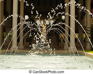 Water fountains arching inward to form a heart shape and colliding in a splash of droplets