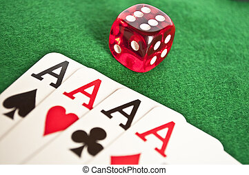 Four aces and red dice on green background
