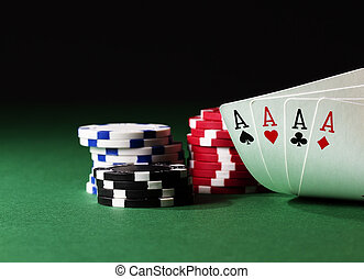 four aces high on green table with chips on black background