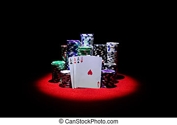 Four aces with gambling chips on red casino table