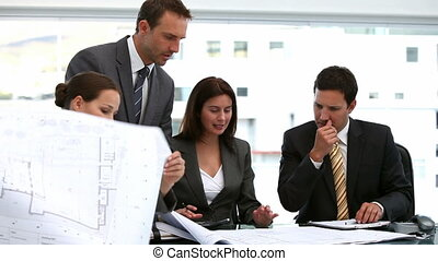 Four architects looking at plans at a table during a meeting