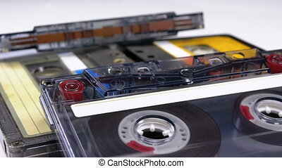 Four Audio Cassettes Rotate on White Background. Yellow and...