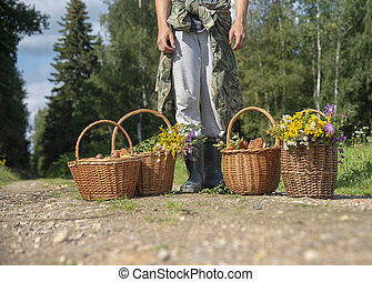 Four baskets of mushrooms and flowers on the forest road