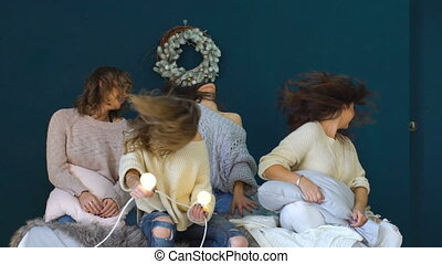 Four beautiful girls dance, shake heads and hair on bed...