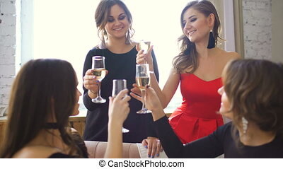 Four beautiful girls drink champagne and cheers. Women having fun laugh in bedroom.