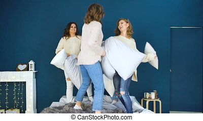 Four beautiful girls fight pillows each other . Girlfriends having fun and laugh in bedroom indoors party