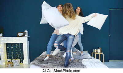 Four beautiful girls fight pillows each other . Girlfriends having fun and laugh in bedroom