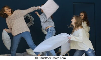 Four beautiful girls fight pillows each other on bed indoors party slowmotion