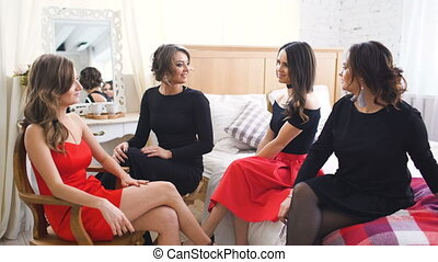 Four beautiful girls have gossip talks while sitting on sofa. Women having fun laugh in bedroom.