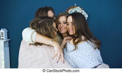 Four beautiful girls hug each other . Girlfriends having fun and laugh in bedroom