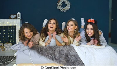 Four beautiful girls lie on bed smiling . Girlfriends having fun and laugh in bedroom