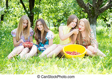 Four beautiful young women girl friends having fun eating strawberries on summer green outdoors background