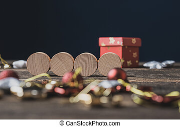 Four blank wooden cut circles in the middle of Christmas setting of baubles and decoration