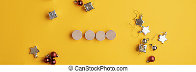 Four blank wooden cut circles placed over yellow background with holiday baubles and stars