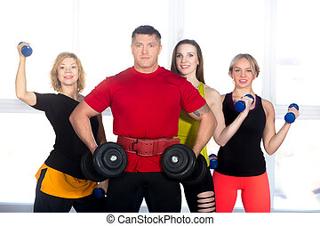 Four bodybuilders standing with dumbbells in gym