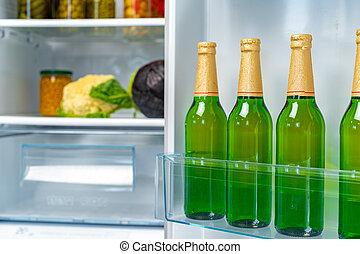 Four bottles of beer on shelf in fridge