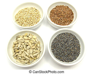 Four bowls with different seeds on a white background